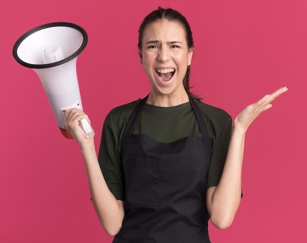 Zirytowana młoda brunetka fryzjerka w mundurze stoi z podniesioną ręką i trzyma głośnik odizolowany na różowej ścianie z miejscem na kopię