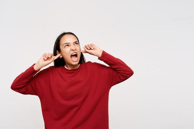 Zirytowana młoda brunetka o długich włosach, zamykająca uszy palcami wskazującymi, patrząc gniewnie w górę, unika głośnych dźwięków podczas pozowania nad białą ścianą