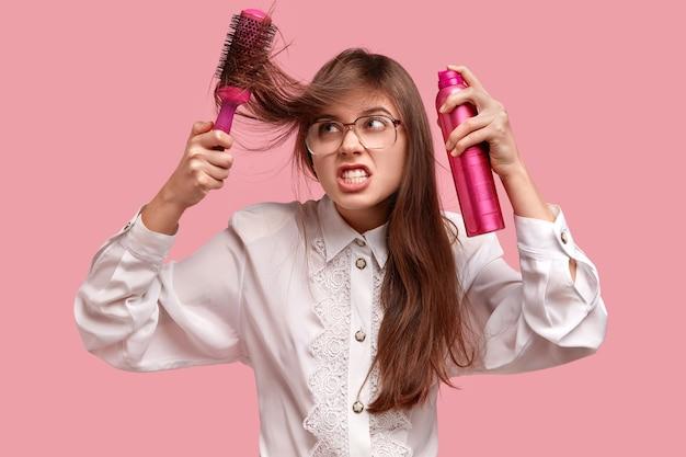 Zirytowana młoda dama układa fryzurę lakierem i szczotką, ma zniszczone włosy