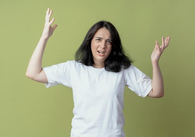 Zirytowana młoda dziewczyna całkiem kaukaski, podnosząc ręce na białym tle na oliwkowym tle