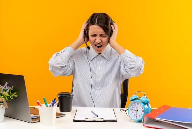 Zirytowana młoda dziewczyna call center noszenie zestawu słuchawkowego siedzi przy biurku, trzymając głowę z zamkniętymi oczami, odizolowane na pomarańczowo