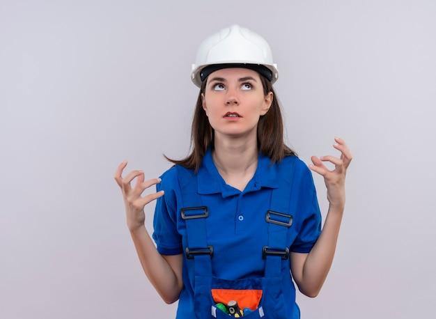 Zirytowana młoda dziewczyna konstruktora w białym kasku i niebieskim mundurze trzyma ręce w górę i patrzy w górę na odosobnionym białym tle z miejsca na kopię