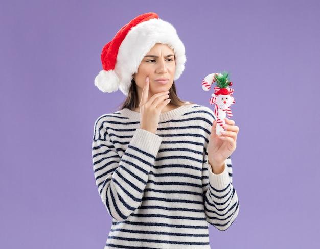 Zirytowana młoda dziewczyna rasy kaukaskiej w kapeluszu mikołaja kładzie rękę na brodzie, trzymając i patrząc na cukierek