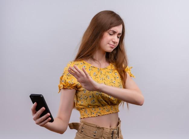 Zirytowana młoda dziewczyna trzyma telefon komórkowy i wskazuje ręką na telefon komórkowy z zamkniętymi oczami