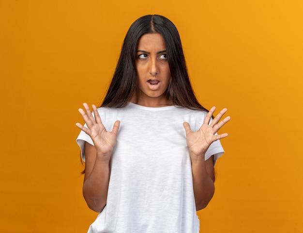 Zirytowana młoda dziewczyna w białej koszulce, patrząca na bok z podniesionymi rękami, szaleje
