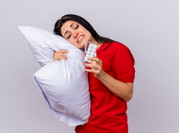 Zirytowana młoda kaukaska chora dziewczyna przytula poduszkę, kładąc na niej głowę z paczką tabletek i szklanką wody w dłoni, patrząc na nie na białym tle z miejsca na kopię