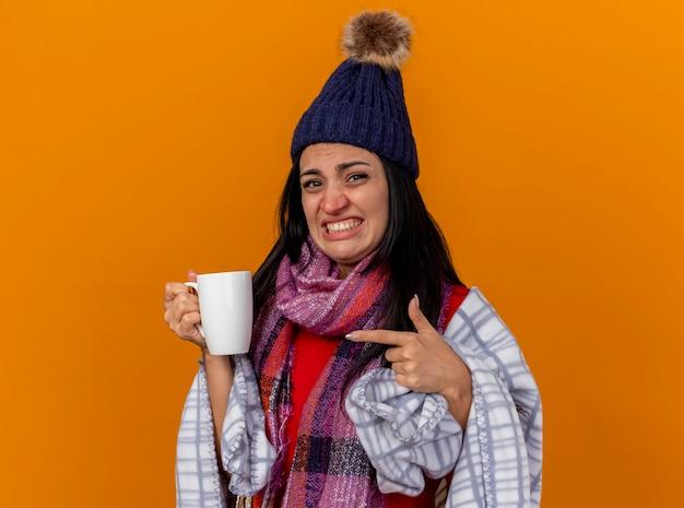 Zirytowana młoda kaukaska chora dziewczyna w czapce zimowej i szaliku owinięta w kratę, trzymając i wskazując na filiżankę herbaty odizolowaną na pomarańczowej ścianie z miejscem na kopię