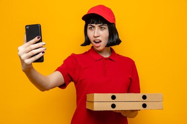 Zirytowana młoda kaukaska dziewczyna dostarczająca pizzę trzyma pudełka po pizzy i krzyczy na kogoś patrzącego na telefon