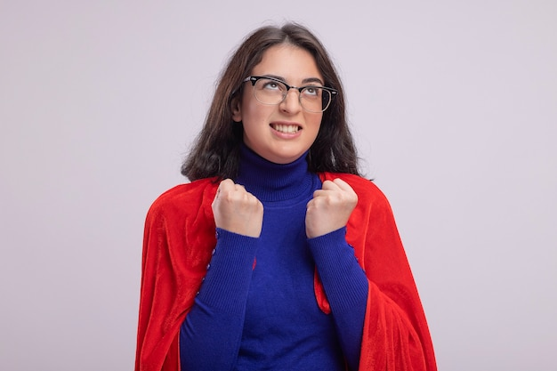 Zirytowana młoda kaukaska dziewczyna superbohatera w czerwonej pelerynie w okularach, zaciskając pięści, patrząc w górę na białym tle na białej ścianie