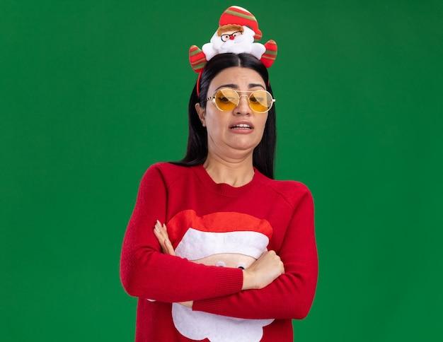 Zirytowana młoda kaukaska dziewczyna ubrana w opaskę świętego mikołaja i sweter w okularach stojąca z zamkniętą postawą patrząc w dół na białym tle na zielonym tle