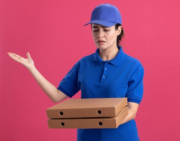 Zirytowana młoda kobieta dostarczająca w mundurze i czapce trzymająca i patrząca na paczki pizzy pokazujące pustą rękę odizolowaną na różowej ścianie