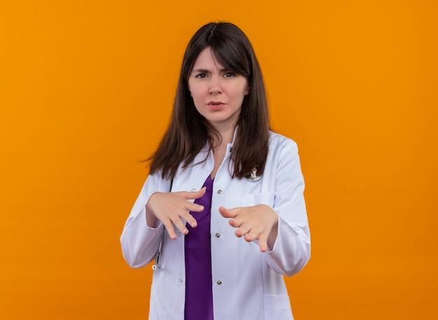 Zirytowana młoda kobieta lekarz w szlafroku medycznym z gestami stetoskopu z dala ode mnie na odosobnionym pomarańczowym tle z miejsca na kopię
