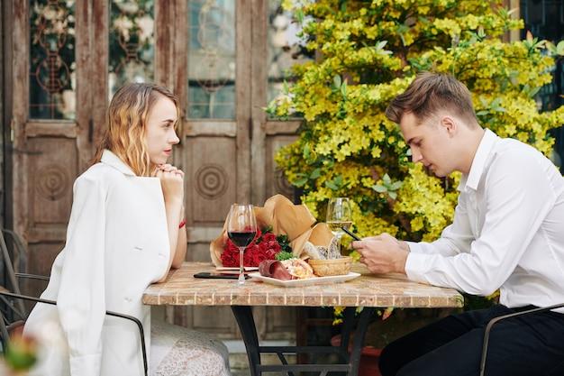 Zirytowana młoda kobieta patrzy na chłopaka, który pisze sms-y do przyjaciół lub sprawdza media społecznościowe, zamiast rozmawiać z nią podczas romantycznej randki