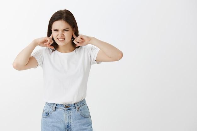 Zirytowana młoda kobieta pozuje przeciw białej ścianie