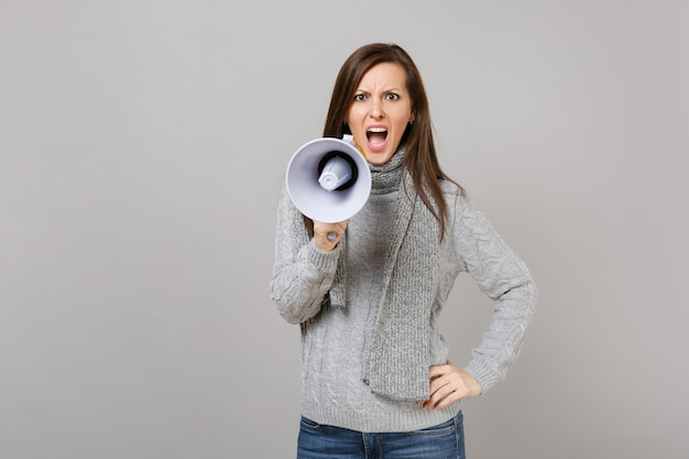 Zirytowana młoda kobieta w szarym swetrze szalik krzyczeć w megafon na białym tle na szarym tle portret studio. ludzie zdrowej mody styl życia szczere emocje, koncepcja zimnej pory roku. makieta miejsca na kopię.