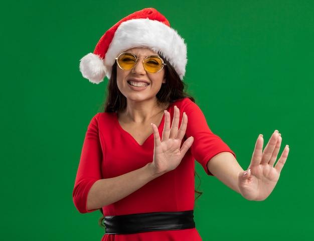 Zirytowana młoda ładna dziewczyna w kapeluszu i okularach świętego mikołaja, wykonująca gest odmowy na zielonej ścianie