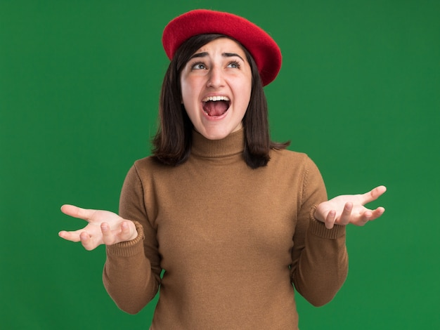 Zirytowana młoda ładna kaukaska dziewczyna w berecie trzyma ręce otwarte i patrzy w górę