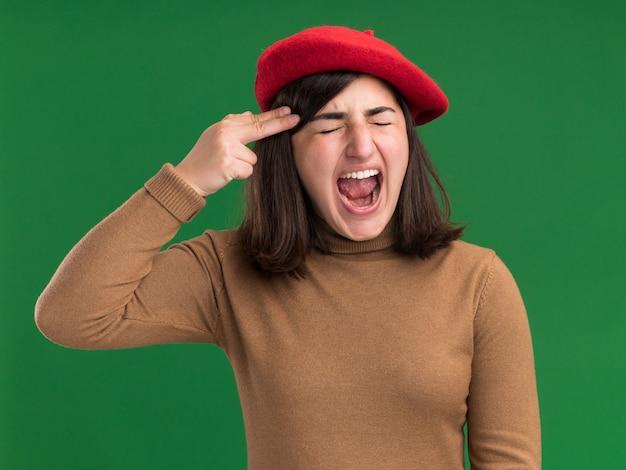 Zirytowana młoda ładna kaukaska dziewczyna z beretowym kapeluszem gestykuluje znak pistoletu umieszczając w świątyni odizolowaną na zielonej ścianie z kopią przestrzeni