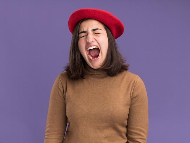 Zirytowana młoda ładna kaukaska dziewczyna z beretowym kapeluszem stoi z zamkniętymi oczami, krzycząc na kogoś odizolowanego na fioletowej ścianie z kopią przestrzeni