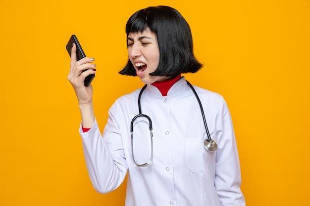 Zirytowana młoda ładna kaukaska kobieta w mundurze lekarza ze stetoskopem trzymająca i patrząca na telefon