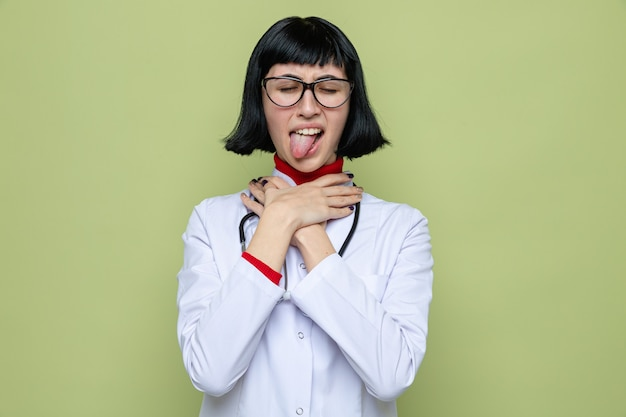 Zirytowana młoda ładna kaukaska kobieta w okularach w mundurze lekarza ze stetoskopem wystającym językiem i dławiąca się rękami