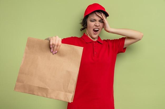 Zirytowana młoda ładna kobieta-dostawca kładzie rękę na czole i trzyma papierowe opakowanie na żywność