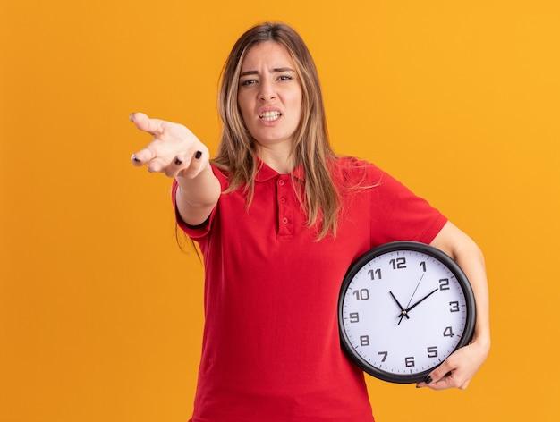 Zirytowana młoda ładna kobieta trzyma zegar i wskazuje z przodu ręką odizolowaną na pomarańczowej ścianie