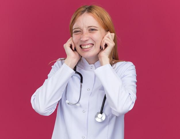 Zirytowana młoda lekarka imbirowa ubrana w szatę medyczną i stetoskop wkładający palce do uszu