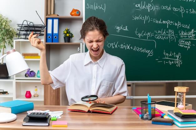 Zirytowana młoda nauczycielka matematyki zdejmująca okulary siedząca przy biurku z przyborami szkolnymi trzymająca lupę trzymająca rękę na otwartej księdze krzycząca z zamkniętymi oczami w klasie