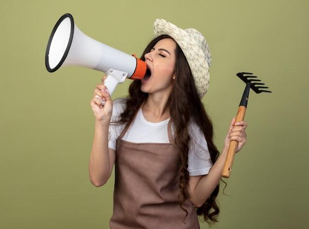 Zirytowana młoda ogrodniczka w mundurze w kapeluszu ogrodniczym trzyma prowizję i krzyczy do głośnika patrząc z boku na tle oliwkowej ściany