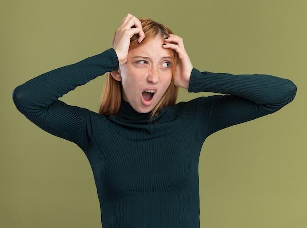Zirytowana młoda rudowłosa ruda dziewczyna z piegami kładzie ręce na głowie i patrzy na bok odizolowaną na oliwkowozielonej ścianie z kopią przestrzeni