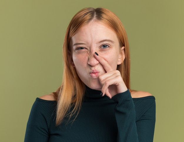 Zirytowana młoda rudowłosa rudowłosa dziewczyna z piegami kładzie palec na nosie i patrzy na aparat na oliwkowym
