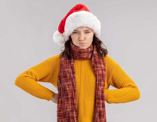 Zirytowana młoda słowiańska dziewczyna w czapce świętego mikołaja i szaliku na szyi kładzie ręce na talii na białym tle na białej ścianie z kopią przestrzeni