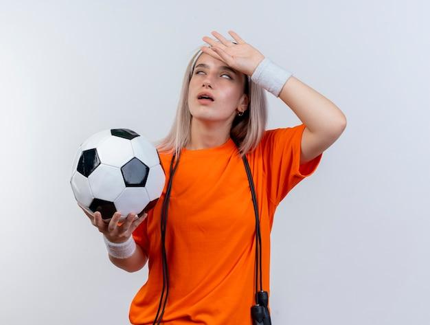 Zirytowana młoda sportowa kobieta z szelkami i skaczącą liną na szyi z opaską na głowę i opaskami na nadgarstki trzyma piłkę i kładzie rękę na czole odizolowanym na białej ścianie