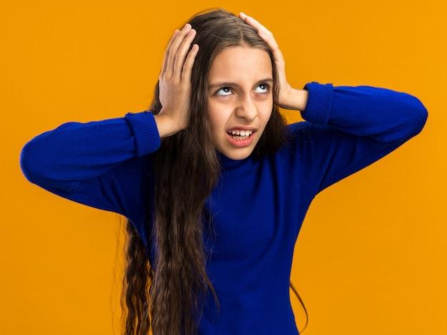 Zirytowana nastolatka trzymająca ręce na głowie patrząca w górę na pomarańczowej ścianie