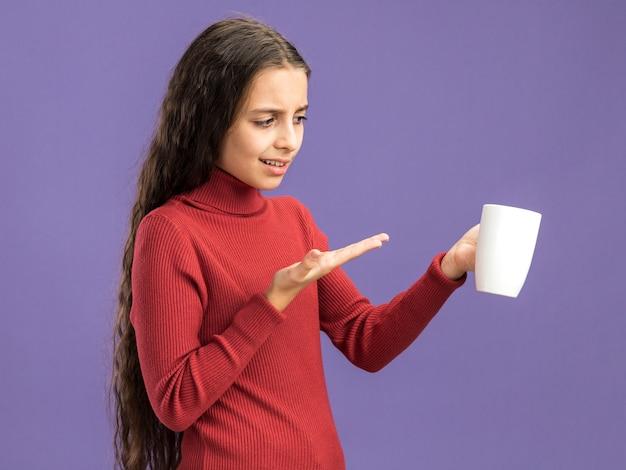 Zirytowana nastolatka trzymająca się patrząca i wskazująca ręką na filiżankę herbaty odizolowaną na fioletowej ścianie