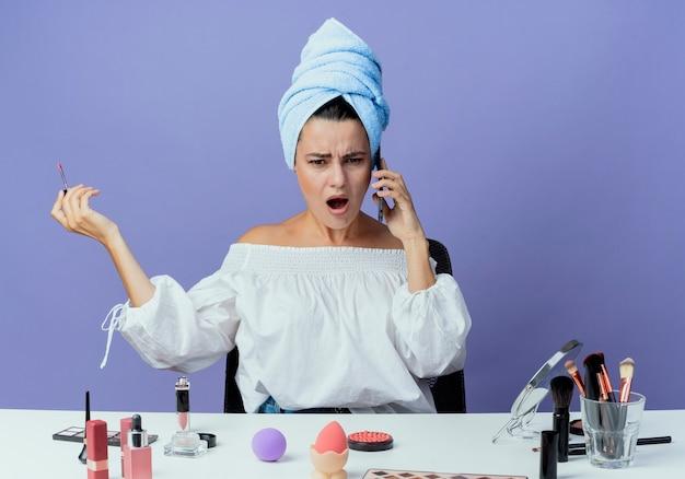 Zirytowana piękna dziewczyna owinięta ręcznikiem do włosów siedzi przy stole z narzędziami do makijażu, trzymając błyszczyk, rozmawiając przez telefon na fioletowej ścianie