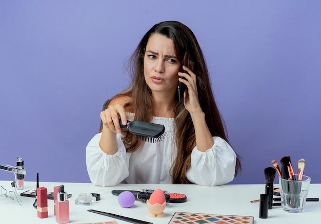 Zirytowana piękna dziewczyna siedzi przy stole z narzędziami do makijażu trzyma grzebień do włosów, rozmawia przez telefon, patrząc na bok na białym tle na fioletowej ścianie