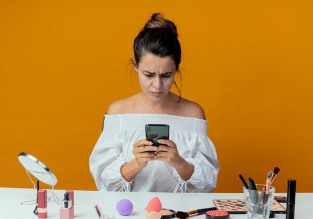 Zirytowana piękna dziewczyna siedzi przy stole z narzędziami do makijażu, trzymając i patrząc na telefon na białym tle na pomarańczowej ścianie
