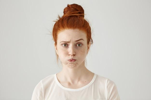 Zirytowana, poirytowana młoda rudowłosa kobieta z piegami na policzkach, marszcząca brwi, sfrustrowana czymś. wyraz twarzy, emocje i uczucia człowieka. koncepcja zmęczenia lub nudy