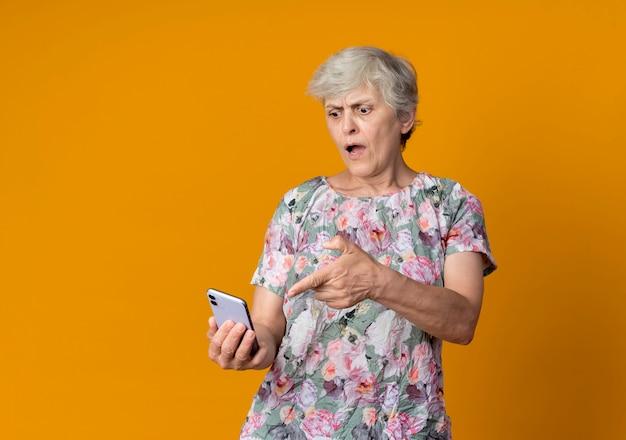 Zirytowana starsza kobieta trzyma i wskazuje na telefon na białym tle na pomarańczowej ścianie
