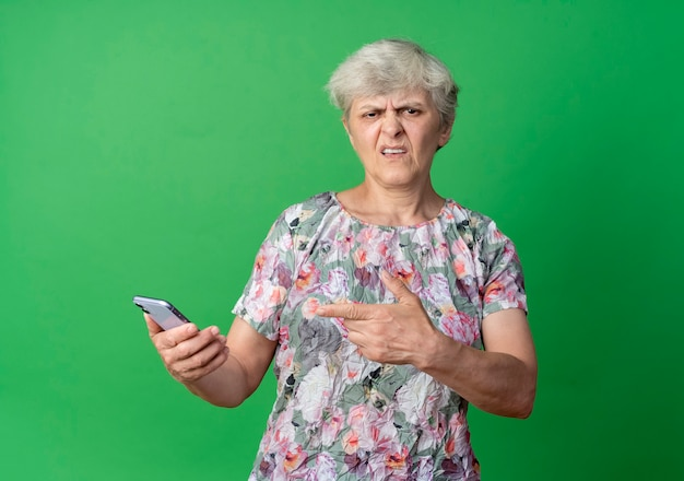Zirytowana starsza kobieta trzyma i wskazuje na telefon na białym tle na zielonej ścianie