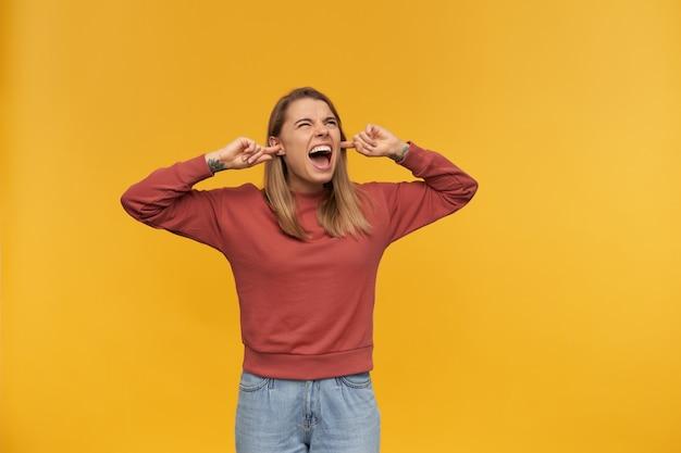 Zirytowana szalona młoda kobieta w zwykłym ubraniu zakryła uszy palcami i krzyczała na żółtej ścianie. wygląda z boku