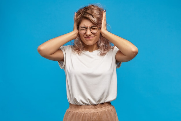Zirytowana, wściekła hipsterka w modnych okularach zakrywających uszy rękami i przykręconych oczu, zirytowana piskliwym dźwiękiem lub głośną muzyką. sfrustrowana nastolatka nie może znieść walki rodziców