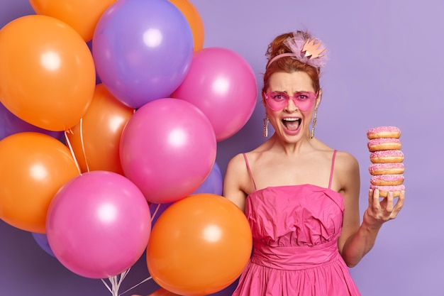 Zirytowana, wściekła rudowłosa kobieta w różowej odświętnej sukience i okularach przeciwsłonecznych w kształcie serca trzyma stos pączków i głośno wykrzykuje pozy z wielobarwnymi balonami z helem