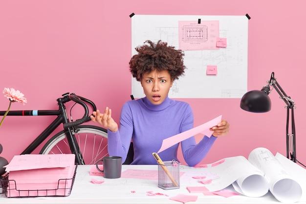 Zirytowana zaintrygowana etniczna inżynierka trzyma papier unosi rękę ma niezadowolony wyraz twarzy pracuje w biurze przygotowuje prace projektowe