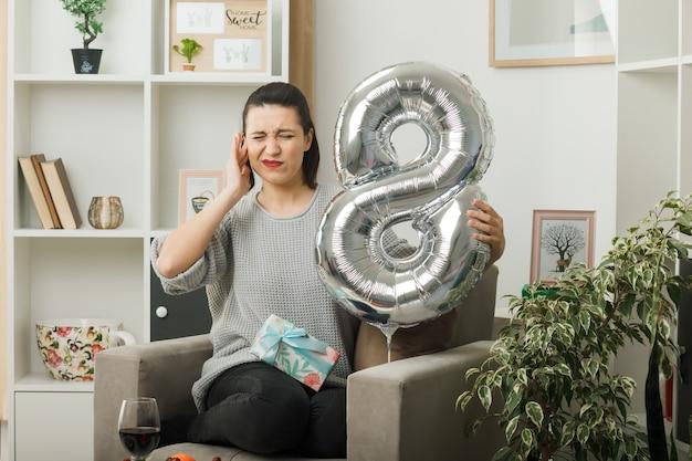 Zirytowana zamknięta ucho piękna dziewczyna w szczęśliwy dzień kobiet trzymająca balon numer osiem siedząca na fotelu w salonie