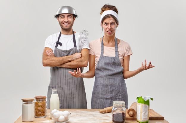 Zirytowana żona podnosi rękę, ma dużo pracy w kuchni, szczęśliwy mężczyzna pomaga w przygotowaniu potrawy, trzyma trzepaczkę, idzie upiec ciasto. dwóch cukierników pracuje w restauracji, ma wielu gości. kulinarna koncepcja