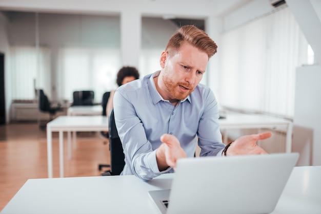 Zirytowany biznesowy mężczyzna patrzeje laptopu ekran.
