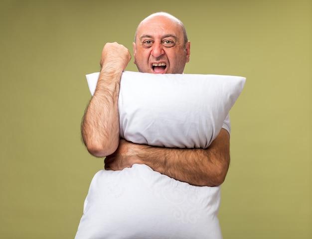 Zirytowany dorosły chory kaukaski mężczyzna trzyma poduszkę i trzyma pięść odizolowany na oliwkowej ścianie z miejsca na kopię